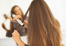 Woman straightening hair with straightener royalty free stock image