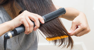 Woman straightening hair with straightener. Royalty Free Stock Photos