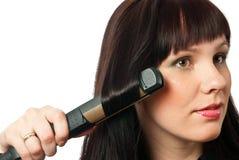 Woman straightening hairs Royalty Free Stock Photos