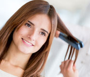 Woman straightening her hair Royalty Free Stock Image