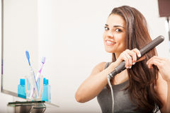Woman straightening her hair with iron Royalty Free Stock Photos