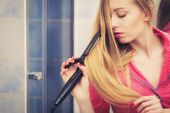 Woman straightening her long blond hair Stock Images