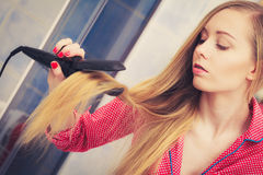 Woman straightening her long blond hair Royalty Free Stock Image