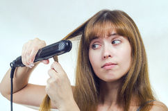 The woman straightens hair the curling iron Royalty Free Stock Photography