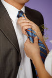 Woman straightens his tie Royalty Free Stock Image