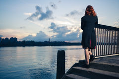 Woman stranding on stairs by river Stock Images