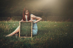 Woman with strange mirror on a meadow Royalty Free Stock Image