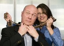 Woman Strangles CoWorker. Businesswoman strangles a male coworker with his necktie royalty free stock photos