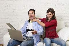 Woman strangling technology freak husband or boyfriend for being electronic devices and internet addiction concept Stock Photo