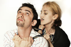Woman  strangling a young man tie Royalty Free Stock Images