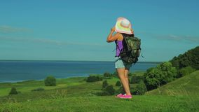94c16adf8b100 A woman in a straw hat with a backpack standing on a mountain and admiring  the