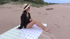 Woman in straw hat on the beach by the sea stock video