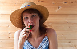 Woman in straw hat with cucumber Stock Image