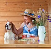 Woman in straw hat with dog Stock Images