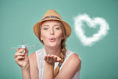 Woman in straw hat holding airplane model in hand Stock Photo