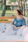Woman in a straw hat. Hot sunny day, a woman in a straw hat sitting on a wooden bench Stock Images