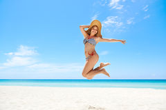 Woman with straw hat jumping mid-air at beach. Portrait of young beautiful girl at tropical beach for vacations, jumping mid-air for joy, looking at camera and Stock Photo