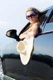 Woman with straw hat leaning from car Royalty Free Stock Photography