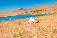 Woman in straw hat lying on dry grass. Young woman in straw hat lying on dry grass near the lake Stock Photography