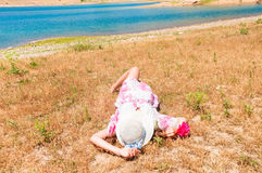 Woman in straw hat lying on dry grass. Young woman in straw hat lying on dry grass near the lake Royalty Free Stock Image
