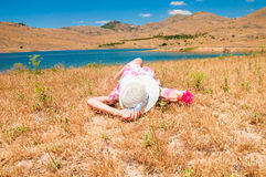 Woman in straw hat lying on dry grass. Young woman in straw hat lying on dry grass near the lake Stock Image