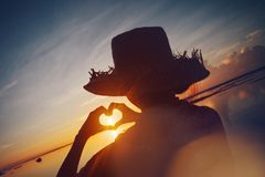 Woman in straw hat making heart symbol with her hands at sunrise near the ocean. Lens flare effect and bright color Royalty Free Stock Image