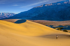 Woman in straw hat  photographing sand waves Royalty Free Stock Photo