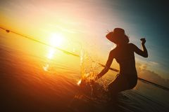 Woman in straw hat playing with water in ocean at sunset. Woman in straw hat playing with water in the ocean at sunset Royalty Free Stock Photos