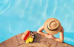 Woman in straw hat in pool with plate og tropical fruits stock images