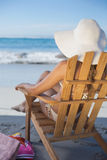 Woman in straw hat relaxing in deck chair on the beach Stock Photo