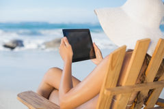 Woman in straw hat relaxing in deck chair on the beach using tablet pc. On a sunny day Stock Photos