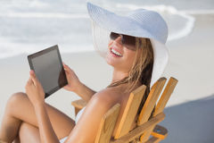 Woman in straw hat relaxing in deck chair on the beach using tablet pc. On a sunny day Stock Photography