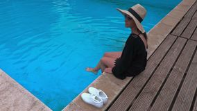 Woman in straw hat relaxing on edge of pool stock video