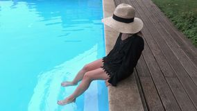 Woman in straw hat relaxing on the edge of swimming pool stock video footage