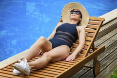 Woman in straw hat relaxing on the lounge chair near the pool Royalty Free Stock Images