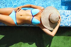 Woman in straw hat relaxing by the pool Stock Photos