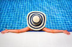 Woman in straw hat relaxing swimming pool royalty free stock photography