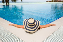 Woman in straw hat relaxing swimming pool Royalty Free Stock Photo