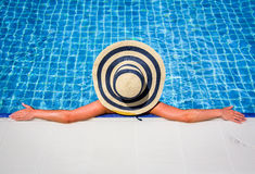 Woman in straw hat relaxing swimming pool Stock Photos