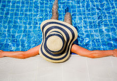 Woman in straw hat relaxing swimming pool stock images