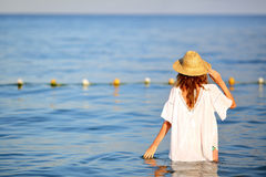 Woman in straw hat in sea water on the beach back to us Royalty Free Stock Photos