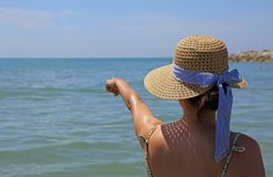 Woman with straw hat shows hand in the horizon of the sea royalty free stock photo