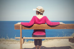 Woman in a straw hat sits on a bench by the sea Royalty Free Stock Images