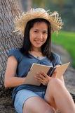 Woman in straw hat sitting by a tree Stock Photo