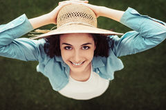 Woman with straw hat. Smiling woman standing outdoors in nature and holding her straw hat, she is smiling at camera, top view Royalty Free Stock Photo