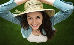 Woman with straw hat. Smiling woman standing outdoors in nature and holding her straw hat, she is smiling at camera, top view Royalty Free Stock Image