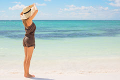 Woman with straw hat standing on the beach Stock Photos