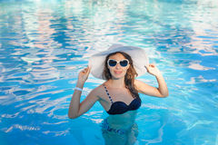 Woman with straw hat and sunglasses in the swimming pool Royalty Free Stock Images