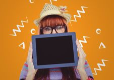 Woman in straw hat with tablet over face against orange background with white patterns Royalty Free Stock Images