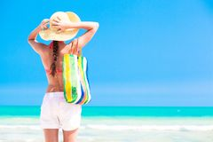 Woman in straw hat and on a tropical beach with Royalty Free Stock Image
